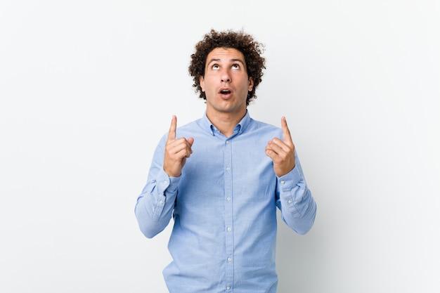 Молодой кудрявый зрелый человек в элегантной рубашке, указывая вверх ногами с открытым ртом.