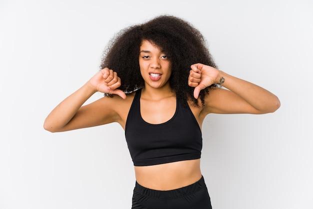 親指を示すと嫌悪感を表現する若いアフリカ系アメリカ人のスポーティな女性。