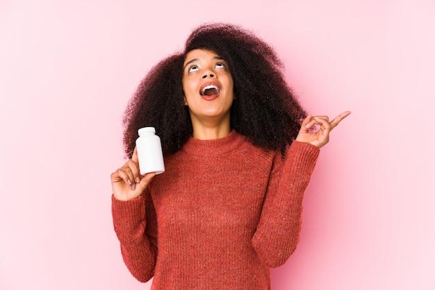 口を開けて逆さまに指しているビタミンを保持している若いアフロ女性。