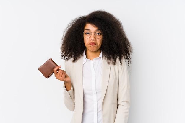 クレジットカードを保持している若いアフロビジネス女性が肩をすくめ、目を開けて混乱しています。