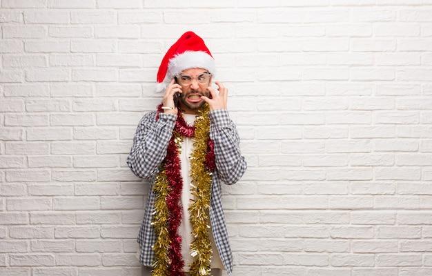 クリスマスの怒りと怒りを祝うプレゼントと一緒に座っている若い男