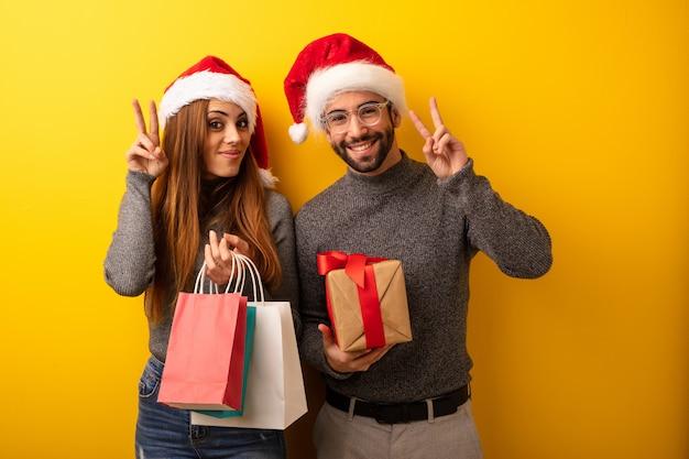 贈り物やショッピングバッグを持っているカップルやお友達、楽しくて幸せ、勝利のジェスチャー
