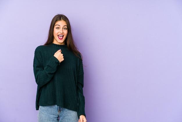 Молодая кавказская женщина изолированная на пурпуре удивила указывать с пальцем, широко улыбаясь.