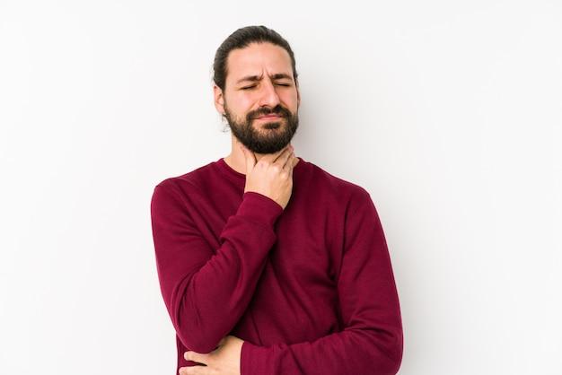 白で隔離された若い長い髪の男は、ウイルスや感染症のために喉の痛みに苦しんでいます。