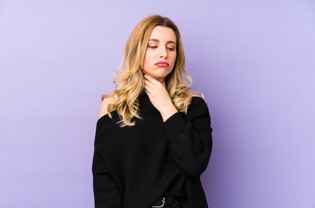 分離された若いブロンドの女性は、ウイルスや感染症のため喉の痛みに苦しんでいます。