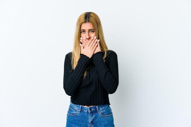 Молодая белокурая женщина изолированная на белом рте заволакивания при руки смотря потревоженный.