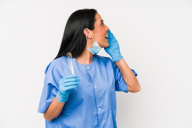 Женщина дантиста изолированная на белизне крича и держа ладонь около раскрытого рта.