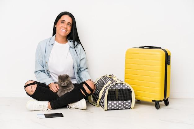 白の幸せ、笑顔、陽気な上に分離されて彼女の猫を持つ旅行者の女性。