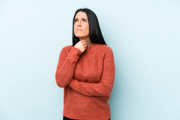 青に分離された若い白人女性は、ウイルスや感染症のため喉の痛みに苦しんでいます。