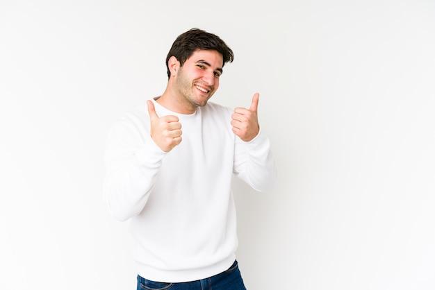 Молодой человек изолированный на белизне поднимая оба большого пальца руки вверх, усмехающся и уверенно.