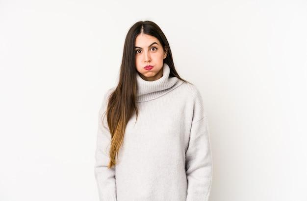 白で隔離される若い白人女性が頬を吹く、疲れた表情をしています。表情のコンセプト。