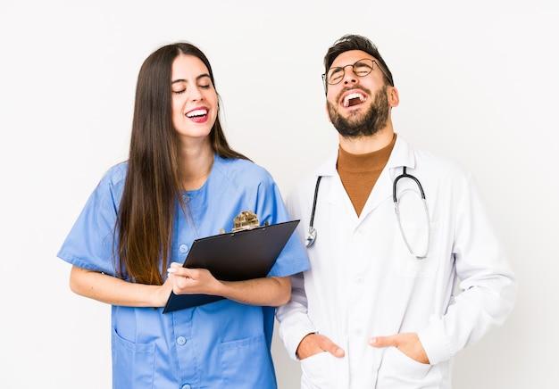 Молодой доктор человек и медсестра изолированные смеется громко держать руку на груди.