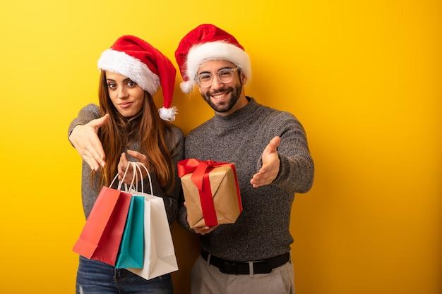 人を迎えるために手を差し伸べる贈り物やショッピングバッグを持っているカップルやお友達