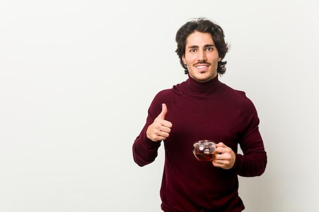 Молодой человек, держа чашку чая, улыбаясь и поднимая палец вверх