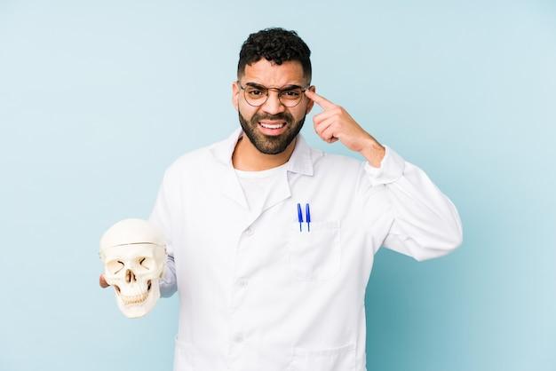 Человек молодого доктора латинский держа череп изолированный показывающ жест разочарования с указательным пальцем.