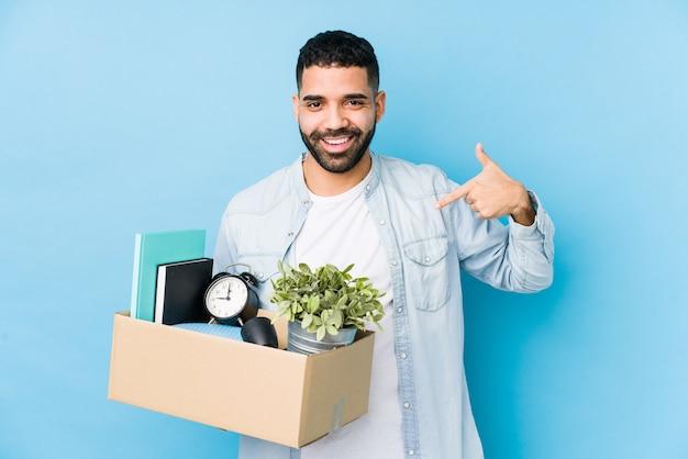 Молодой арабский человек, переезда в новый дом изолированных человек, указывая рукой на рубашку копирования пространство, гордый и уверенный
