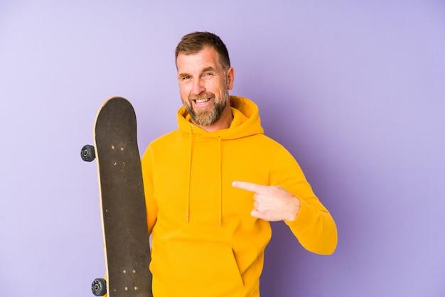 シャツコピースペースを手で指している紫色の人、誇りと自信を持って分離されたシニアスケーター男