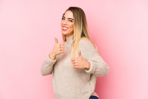 Среднего возраста женщина над изолированных повышение как большие пальцы вверх, улыбаясь и уверенно.