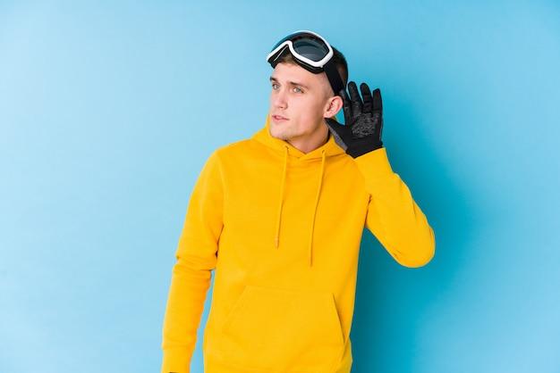 ゴシップを聴こうとしている若いスキーヤーの男。