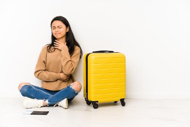 分離されたスーツケースで床に座っている若い中国人旅行者の女性は、ウイルスや感染症のために喉の痛みに苦しんでいます。