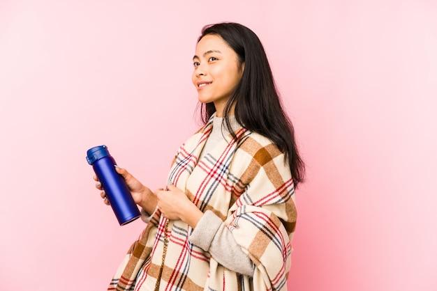 Молодая китайская женщина делая располагаться лагерем изолированный на пинке смотря косой с сомнительным и скептическим выражением.