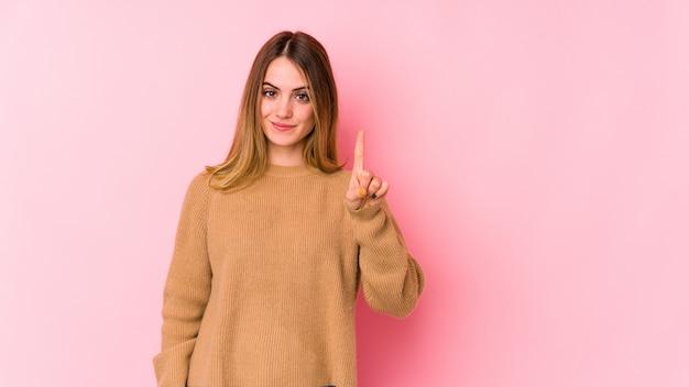 指でナンバーワンを示すピンクに分離された若い白人女性。