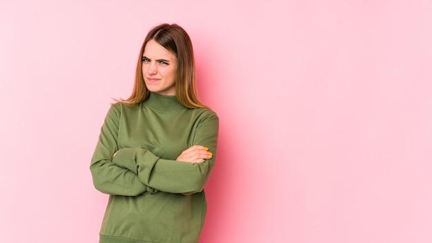 皮肉な表現に不満のピンクに分離された若い白人女性。