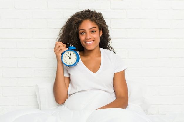 幸せ、笑顔、陽気な目覚まし時計を持ってベッドに座っている若いアフリカ系アメリカ人女性。