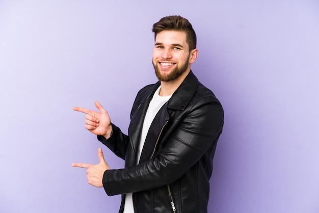 Молодой человек изолированный на пурпуре возбужденный указывать с указательными пальцами прочь.