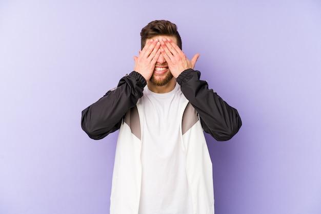 Молодой человек кавказской, изолированных на фиолетовый охватывает глаза руками, широко улыбаясь, ожидая сюрприз.