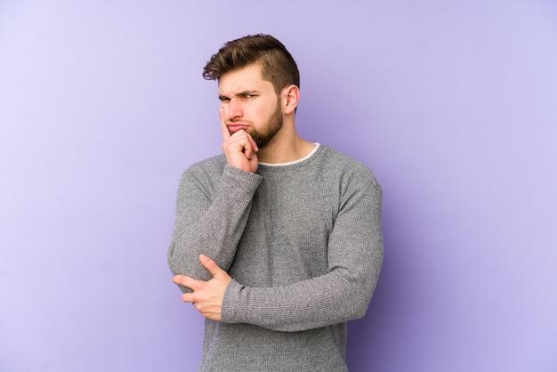 Молодой кавказский человек изолированный на пурпуре созерцая, планируя стратегию, думая о пути дела.
