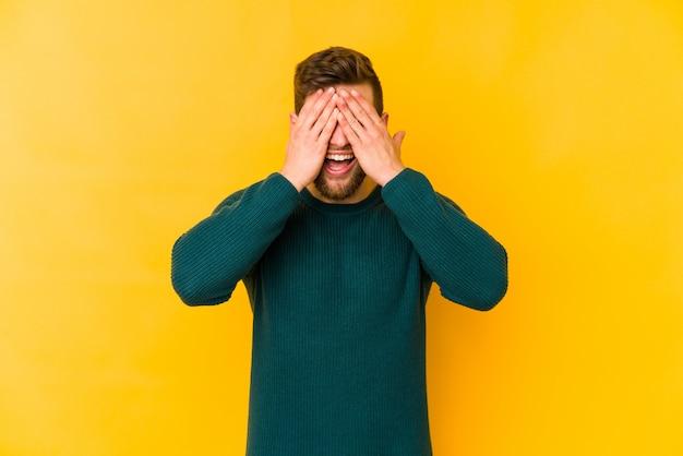 Молодой человек кавказской, изолированные на желтый покрывает глаза руками, широко улыбается, ожидая сюрприз.