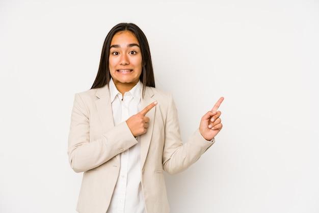 コピースペースに人差し指で指しているショックを受けた白に分離された若い女性。