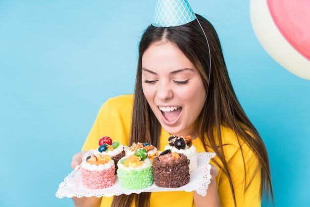 カップケーキトレイを保持している若い白人女性