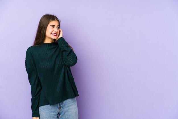 手で耳を覆う紫の壁に若い白人女性。