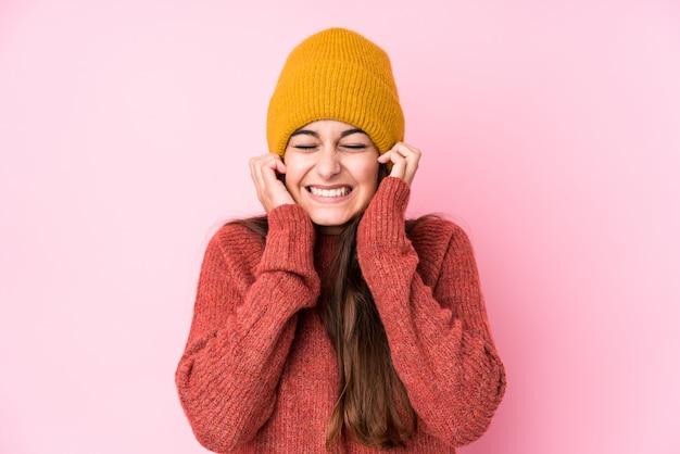 Молодая кавказская женщина нося шерстяную шапку, охватывающих уши руками.
