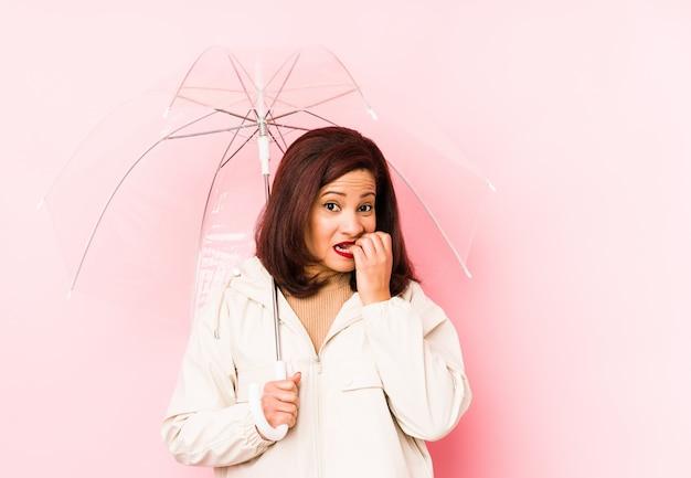 中年のラテン女性が傘をさして、爪を噛み、神経質で非常に心配していた。