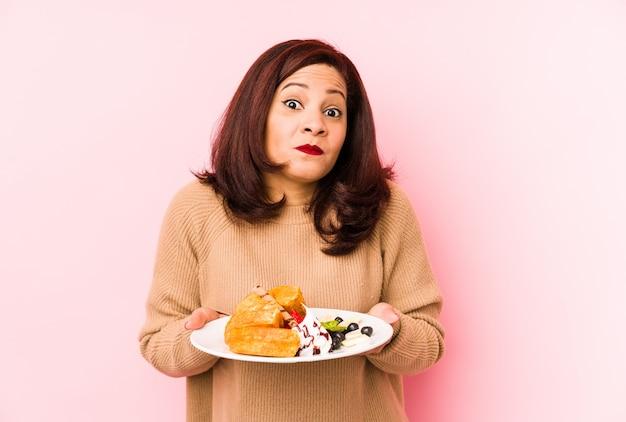 Латинская женщина среднего возраста, держащая вафлю, пожимает плечами плечи и смущает открытые глаза.