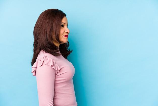 Среднего возраста латинская женщина изолированы глядя влево, боком позе.