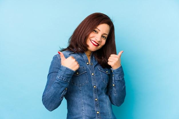 Среднего возраста латинской женщина, изолированных на синем, поднимая оба больших пальца вверх, улыбаясь и уверенно.