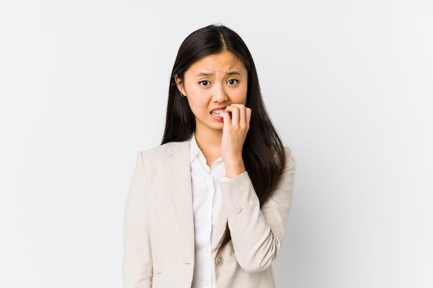 若い中国人ビジネスウーマンは、痛烈な爪を、神経質で非常に心配して隔離しました。