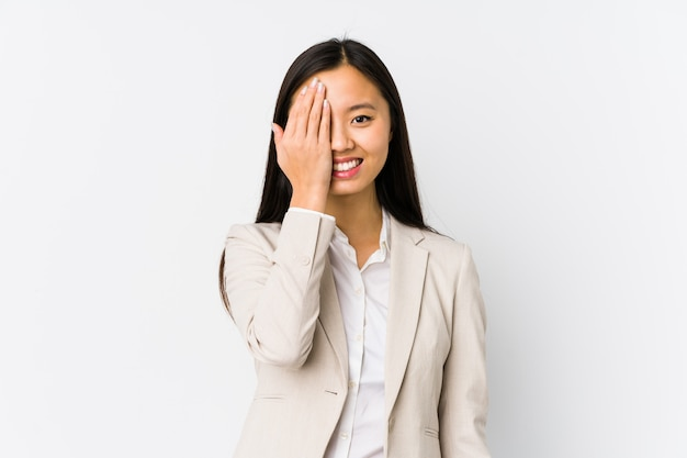 若い中国のビジネス女性が手のひらで顔の半分をカバーして楽しんで分離しました。