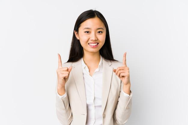 分離された若い中国のビジネスの女性は、空白を示すまで両指で示しています。