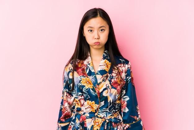 Молодая китайская женщина нося пижаму кимоно изолировала щеки ударов, утомленное выражение. концепция выражения лица.