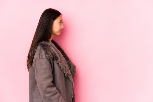 Молодая китайская женщина нося пальто изолировала пристальный взгляд левый, косое представление.