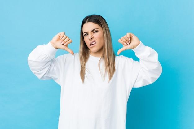 若い白人女性を分離した親指を示すと嫌悪感を表現します。