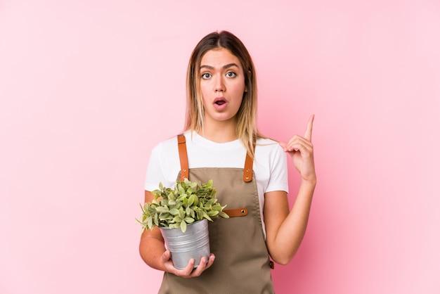 Молодая кавказская женщина садовника в розовой стене имея некоторую отличную идею