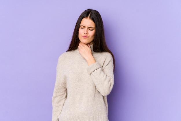 紫色の壁に若い白人女性がウイルスのため喉の痛みに苦しんでいます。