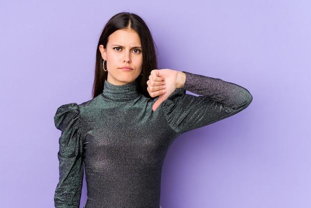 親指ダウンを示す紫色の壁に若い白人女性