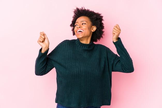 ダンスと楽しいピンクの壁に対して中年のアフリカ系アメリカ人女性。